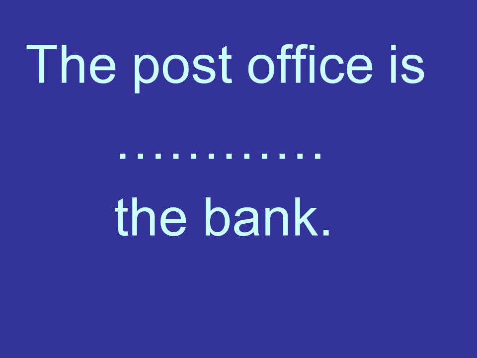 The post office is ………… the bank.